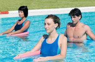 pessoas ativas fazendo ginástica aquática em uma piscina foto