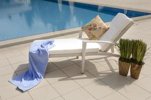 espreguiçadeira ao lado da piscina em um hotel de luxo