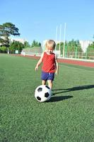 menina bebê loiro jogando futebol foto