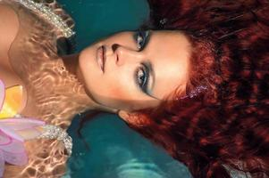 retrato de menina ruiva bonita na água foto