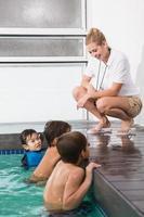 lindos filhos na piscina ouvindo treinador foto