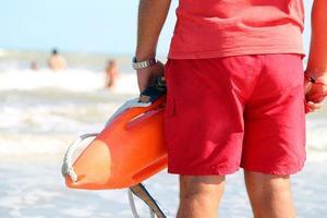 salva-vidas com a lata de resgate para resgatar os nadadores foto