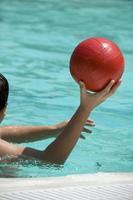 segurando uma bola de polo aquático foto