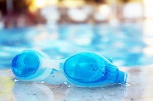 óculos azuis à beira da piscina