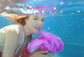 jovem mulher bonita com flor rosa debaixo d'água foto