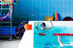 o garoto que aprende a nadar na piscina foto