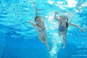crianças nadam na piscina debaixo d'água, meninas se divertem na água foto