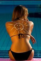 garota na piscina com smiley nas costas foto