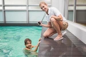 treinador de natação bonita mostrando menino seu tempo foto