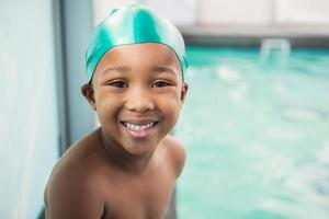 menino bonitinho sorrindo para a piscina foto