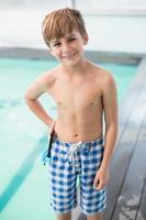 menino bonitinho em pé à beira da piscina