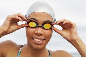corredor sorridente em óculos de proteção e touca de natação foto
