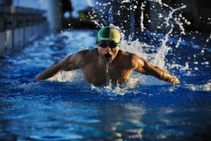 um nadador com boné e óculos saindo da água foto