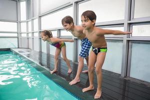 aula de natação bonito prestes a pular na piscina foto