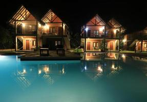 cena noturna com piscina e casas foto