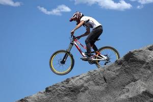 esportista em roupas esportivas em uma bicicleta de montanha passeios nas pedras foto