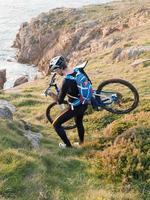 ciclista carregando sua bicicleta na costa galega. foto