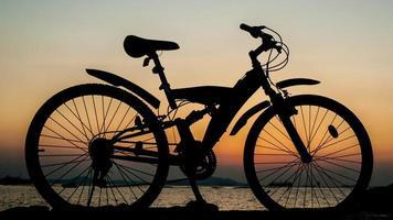 silhueta de bicicleta de montanha, estacionamento no cais ao lado do mar foto