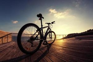 silhueta de bicicleta de montanha ao pôr do sol foto