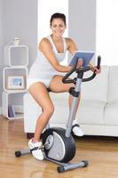 jovem mulher treinando na bicicleta ergométrica foto