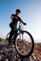 ciclista andando de bicicleta de montanha na trilha rochosa foto