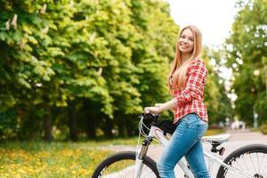 senhora loira com sua bicicleta foto