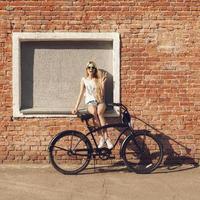 mulher jovem e bonita com bicicleta ao ar livre foto