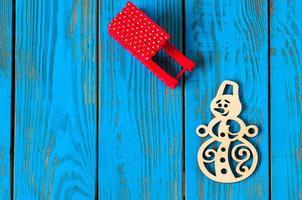 trenó vermelho e boneco de neve artesanal sobre fundo azul de madeira. natal foto