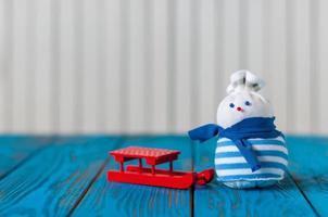trenó vermelho e pequeno boneco de neve artesanal na luz de fundo de madeira foto