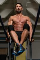 ajuste atleta fazendo exercício em barras paralelas foto