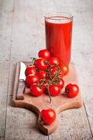 suco de tomate em vidro e tomates frescos foto