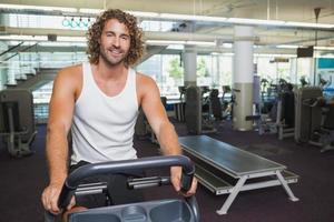 homem bonito malhando na bicicleta ergométrica no ginásio foto