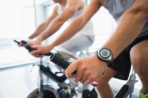seção intermediária de homens trabalhando em bicicletas de exercício no ginásio foto