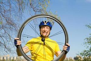 senior sorridente, olhando através de um pneu de bicicleta foto