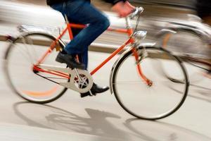 homem na bicicleta laranja foto
