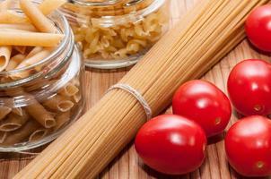 dois potes de vidro com macarrão, espirais e tomate cereja foto