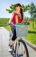 jovem mulher esportiva com compras em uma bicicleta de cesta foto