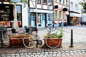 bicicleta feminina rosa estacionada na rua perto de café. foto