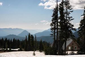 casa de madeira entre as árvores em um fundo de montanhas