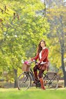 linda fêmea de bicicleta no parque foto