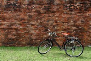 bicicleta vintage e parede de tijolo vermelho foto