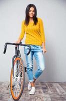 mulher feliz stnading com bicicleta foto