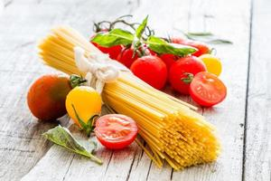 macarrão cru, tomate, manjericão foto