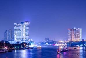 edifício da cidade de Banguecoque à noite. rio na cidade. foto