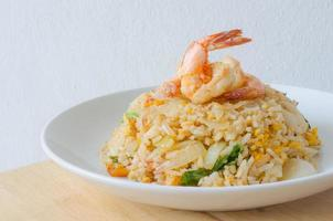 arroz frito com camarão em um prato branco foto
