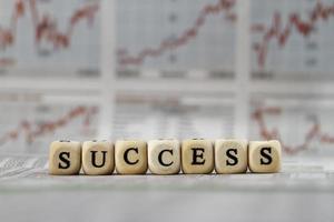 palavra de sucesso construída com cubos de letra no fundo do jornal foto