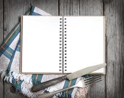 livro de receitas de cozinha em branco na mesa de madeira foto
