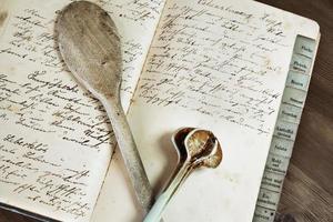 livro de receitas antigo com duas colheres de pau foto