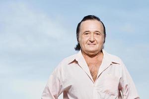 homem sênior em uma camisa rosa foto