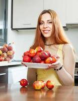 jovem dona de casa segurando nectarinas